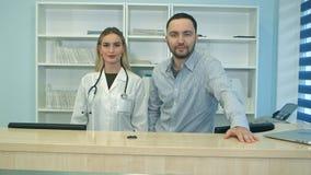 Enfermeras amistosas del varón y de la hembra detrás del mostrador de recepción en hospital Fotos de archivo