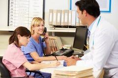 Enfermeras del doctor With dos que trabajan en la estación de las enfermeras Foto de archivo libre de regalías