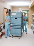 Enfermeras que empujan la carretilla en vestíbulo del hospital Foto de archivo libre de regalías