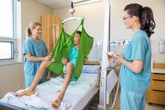 Enfermeras que miran al paciente que se sienta en el paño de imágenes de archivo libres de regalías