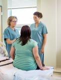 Enfermeras y mujer embarazada que comunican adentro Foto de archivo libre de regalías