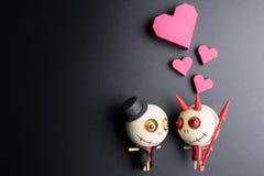 Enfermez dans une boîte la forme rouge de coeur et le diable en bois sur le fond noir avec la Co Photos stock