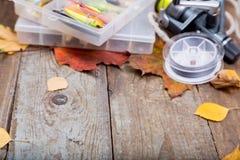 Enfermez dans une boîte les articles de pêche à bord avec l'automne de feuilles Photographie stock