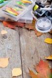 Enfermez dans une boîte les articles de pêche à bord avec l'automne de feuilles Photo libre de droits