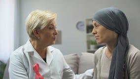 Enfermo de cáncer favorable del doctor de sexo femenino, dando la esperanza de la curar de enfermedad almacen de video