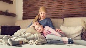 Enfermo de cáncer joven de la hembra adulta que pasa tiempo con su hija en casa, relajándose Concepto de la ayuda del cáncer y de imágenes de archivo libres de regalías