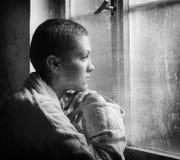 Enfermo de cáncer joven que mira a través de ventana del hospital en el negro Imagenes de archivo
