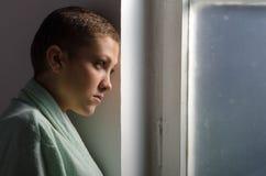 Enfermo de cáncer joven que se coloca delante de ventana del hospital Foto de archivo