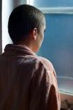 Enfermo de cáncer joven que se coloca delante de ventana del hospital Imágenes de archivo libres de regalías