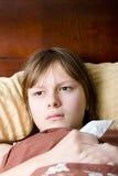 Enfermo de la muchacha del adolescente con la gripe que miente en cama Foto de archivo libre de regalías