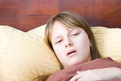 Enfermo de la muchacha del adolescente con la gripe que miente en enfermedad de la cama Imágenes de archivo libres de regalías