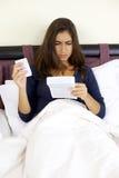 Enfermo de la mujer joven en la lectura de la cama sobre medicina Foto de archivo
