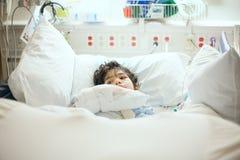 Enfermo de mentira del niño pequeño discapacitado en cama de hospital Fotos de archivo