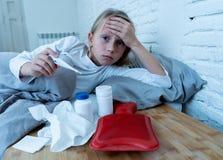 Enfermo de mentira de la niña en la sensación de la cama enferma con alta fiebre y el dolor de cabeza que tiene una gripe fría fotografía de archivo