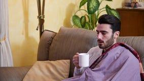 Enfermo del hombre joven con infusión de hierbas de consumición de la gripe metrajes
