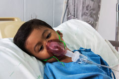 Enfermo del muchacho en la máscara del inhalador para el niño Fotos de archivo libres de regalías