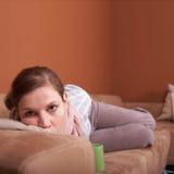 Enfermo en un sofá Imágenes de archivo libres de regalías