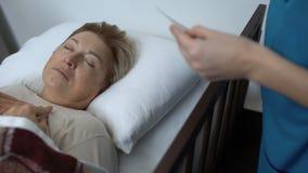 Enfermo-enfermera que cubre al paciente mayor durmiente con la manta, tomando la foto de familia almacen de metraje de vídeo