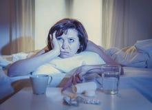 Enfermo pelirrojo de la mujer en cama con la medicina Foto de archivo libre de regalías