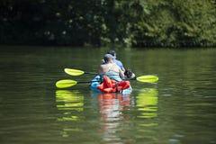 Enfileiramento da mulher e do cão do homem no caiaque no lago quieto Lacamas fotos de stock royalty free