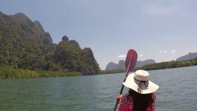 Enfileiramento da mulher que kayaking na opinião traseira traseira do pov da câmera da ação da lagoa a menina que rema no barco d vídeos de arquivo