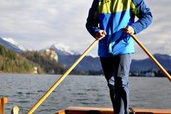 Enfileiramento do homem no barco de madeira típico Pletna no lago sangrado, Eslovênia, no por do sol Turismo, esporte, conceito d foto de stock