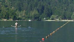Enfileiramento masculino no lago tranquilo, competência do atleta de barco profissional, competição filme