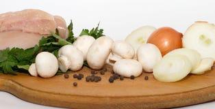enfileire a carne da galinha, a salsa verde, os cogumelos, a grande cebola e as ervilhas da pimenta preta na placa de madeira Foto de Stock Royalty Free
