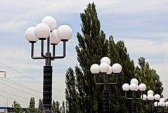 Enfileire com máscaras redondas brancas em luzes de rua na rua Imagem de Stock Royalty Free