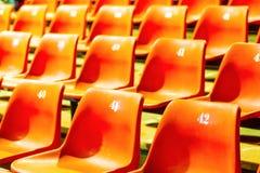 Enfileire a laranja plástica da cadeira com todos os números no grande ro da conferência imagens de stock