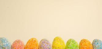 Enfileire ovos da páscoa com luz da mola - fundo amarelo fotografia de stock