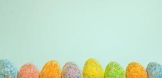 Enfileire ovos da páscoa com luz da mola - fundo azul imagem de stock