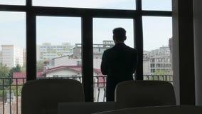 Enfoca adentro el hombre de negocios que mira fuera de la ventana almacen de metraje de vídeo