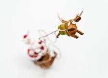 Enfoca adentro el reno con el montar a caballo de Papá Noel en trineo foto de archivo