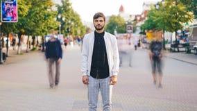 Enfoca adentro el time lapse del hombre de negocios joven en la ropa de moda que se coloca en calle peatonal y que mira la cámara metrajes