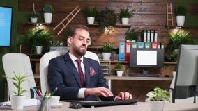 Enfoca adentro el tiro del hombre de negocios que trabaja solamente en oficina con diseño moderno almacen de metraje de vídeo