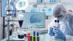 Enfoca adentro el tiro del investigador del cient?fico en el laboratorio de gama alta profesional que mira en el microscopio almacen de video