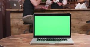 Enfoca adentro el tiro en el ordenador portátil con la pantalla verde almacen de video