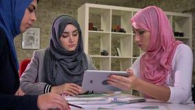 Enfocado sentándose tres hembras árabes están sosteniendo la tableta y están señalando en ella, las negociaciones de trabajo, las almacen de metraje de vídeo