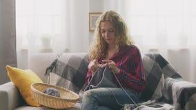 Enfocan adentro de mujer joven el sentarse en el sofá y el hacer punto en hogar almacen de metraje de vídeo