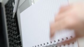 Enfocan adentro en la tabla de trabajo con la planta verde en pote gris, las manos femeninas abren un cuaderno metrajes