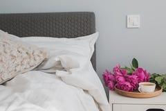 Enfoncez avec les draps blancs et les pivoines et le café roses sur le nightstand Photo stock