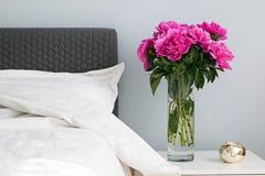 Enfoncez avec les draps blancs et les pivoines roses sur le nightstand Photographie stock libre de droits