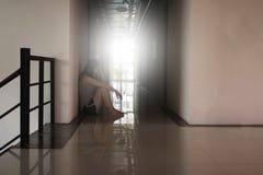 Enfoncez et femme désespérée s'asseyant dans l'obscurité Photos libres de droits