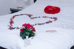 Enfoncez la suite avec une couverture blanche, un coussin rouge, un bouquet des roses rouges et des pétales sous forme de coeur Image stock