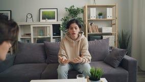 Enfoque adentro del adolescente emocional que comparte problemas con el terapeuta en oficina almacen de video