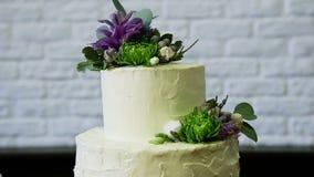 Enfoque adentro en la torta blanca de dos niveles adornada con las flores almacen de metraje de vídeo