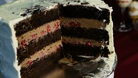 Enfoque adentro en la torta de chocolate grande cortada con caramelo y la cereza almacen de metraje de vídeo