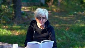 Enfoque adentro en una mujer de mediana edad que lee un libro almacen de metraje de vídeo