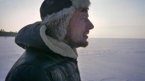 Enfoque amplio en tiro del hombre alegre en perfil que camina rightwards en sol en campo nevoso almacen de video